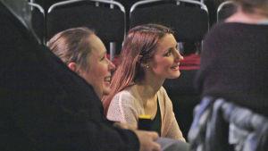 Maria Kramar von Numers sitter mitt i en grupp av människor och ser glad ut.