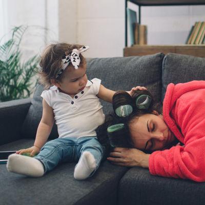 Väsynyt äiti sohvalla, lapsi silittää äidin päätä