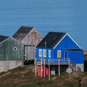 En bild på Grönland med ett litet isberg och hus.