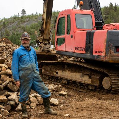 Kullankaivaja Raimo Kanamäki seisoo kaivinkoneensa edessä.
