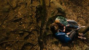 Tre flickor ligger nära varandra på marken i skogen.