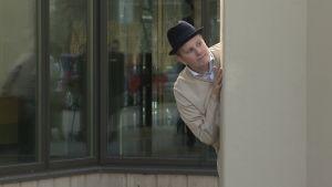 En man i svart hatt tittar om kusten är klar, om han kan rymma (från en performance om Åbo fångläger).