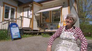 Kvinna sitter framför skärgårdsbutik.