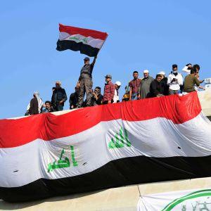 Irakier står på mur och håller upp flagga.