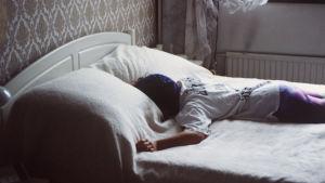 Ihminen nukkuu vatsallaan vuoteessa