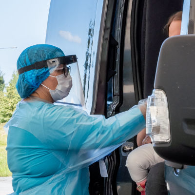 En skötare i skyddsutrustning sträcker sig in i en bil där en person som ska coronatestas sitter.