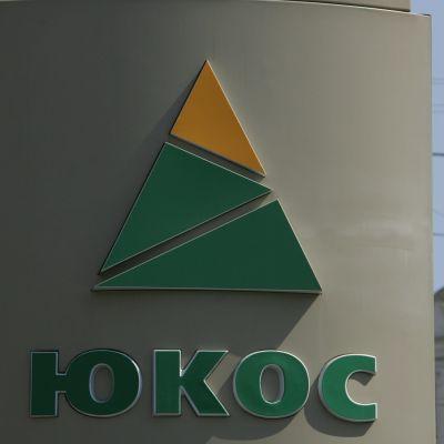 Oljebolagets Yukos varumärke på en vägg i bakgrunden syns ett kyrktorn