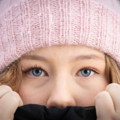 Nuori nainen kurkkaa pipon ja takin välistä.