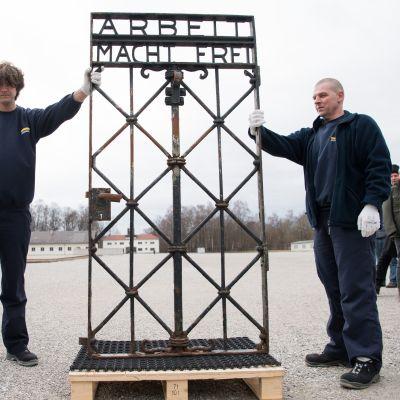 Dachaun keskitysleirin rautaportti varastettiin vuonna 2014. Norjasta joulukuussa löytynyt portti on saatu takaisin museoalueena toimivalle keskitysleirille. Kuvassa kaksi miestä esittelee rautaporttia, jossa lukee Arbeit macht frei.