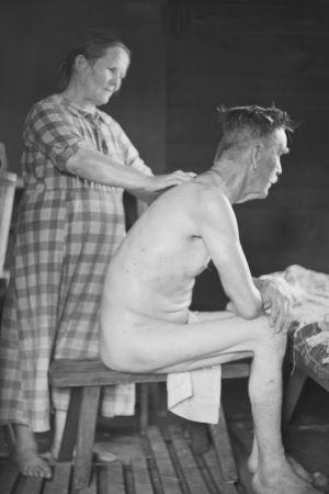 Svartvit bild på en kvinna som tvättar ryggen på en man i Särkijärvi på 1930-talet.