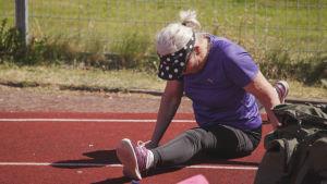 Nainen venyttää itsensä spagaattiin urheilukentällä.