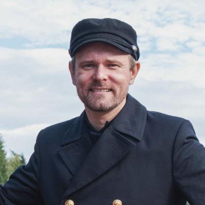 Mies merikapteenin univormussa seisoo punaiseksi maalatun rautalaivan keulassa ja hymyilee. Vierellä on pelastusrengas jossa lukee teksti S/S KOUTA.