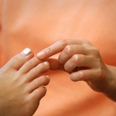 Person behandlas med zonterapi i tårna.