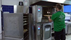 En man sätter in förgräddat bröd i ugnen i en matbutik.