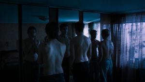 Tre pojkar med bar överkropp står framför en stor spegel i ett halvmörkt rum och tittar på sig själva.