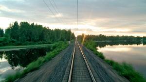 Rautatiekiskot kesäyönä junan veturista kuvattuna.
