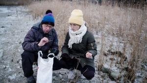 Nainen ja mies kyykistyneenä maahan tarkkailemaan muovinpalasta muovipussi kädessä.