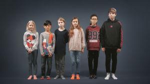 Kuusi eripituista lasta seisoo rivissä.