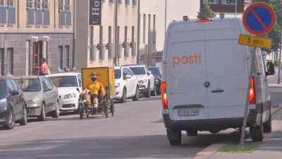 Ett cykelbud med gul skjorta sitter i sin cykel med pedalerna framför sig och en stor gul låda bakom sig. Han cyklar förbi en av Postens bilar.