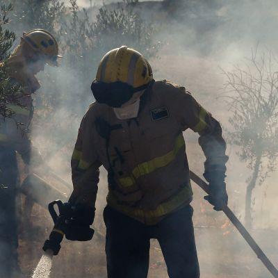 Två brandmän släcker markbränder i Katalonien.