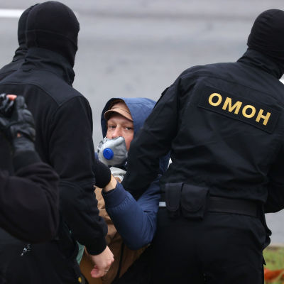 Poliisit kantavat kasvomaskilla suojautunutta mielenosoittajaa