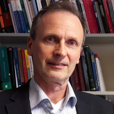 Professor Kimmo Nuotio står framför en bokhylla.