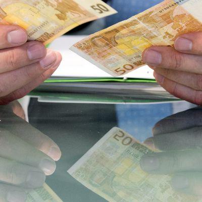 Euron seteleitä miehen kädessä.