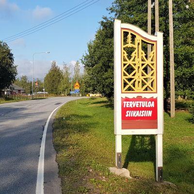 Tervetuloa Siikaisiin -kyltti ennen Siikaisten keskustaa ja kyläraittia.
