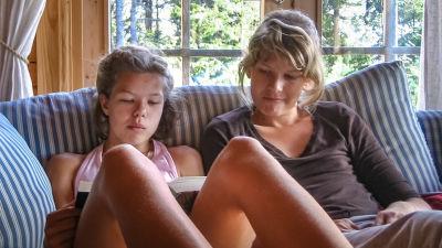 Sara sitter i soffan med sin lillasyster som läser en bok.