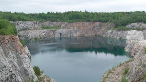 En sjö syns mitt på bilden med kalkstensberg runt omkring och skog i bakgrunden. Svartå kalkstensbrott.