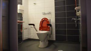 Nya Almahemmets rymliga toalett med dusch och gråa och vita kakel på väggarna.