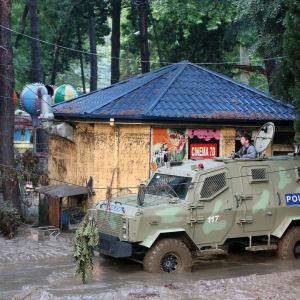 Polisbil på en översvämmad gata i Tbilisi, Georgien.