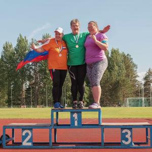 Kolme naista tuulettaa urheilukentällä palkintokorokkeella seisten, mitalit kaulassaan, yhdellä olkapäillä Venäjän lippu.