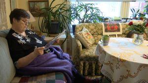Ingrid Hollmérus-Nilsson sitter i en soffa och läser.