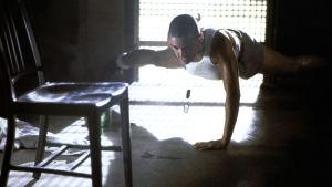 Jordan O'Neill (Demi Moore) tränar armhävningar på golvet med en arm.