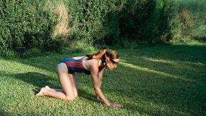 Nuori nainen nelinkontin nurmikolla.side silmillä. Kuva elokuvasta Koiranhammas (Kynodontas eli Dogtooth).