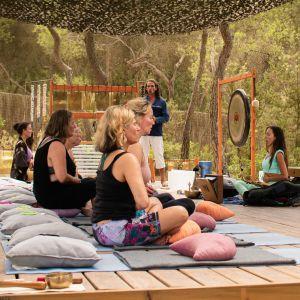 Kuvassa meditaatioretriitin osallistujat istuvat maassa risti-istunnassa silmät kiinni. Heidän edessään ohjaaja ja suuria rumpujaö.