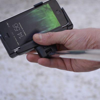 Mies asettelee selfie-keppiä ja kännykkää kuvausvalmiuteen.