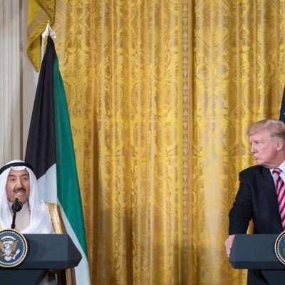 Donald Trump katsoo kohti miestä, joka puhuu mikrofoniin. Taustalla yhdysvaltain ja Kuwaitin liput.