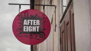 Rund skylt hänger ovanför dörr. På skylten står After Eight.