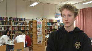 Profilbild på Joar Bergholm, flera ungdomar sitter i bakgrunden av bilden.