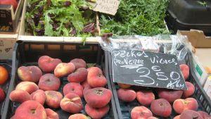Persikoita ja villiä salaattia nizzalaisella toritiskillä.