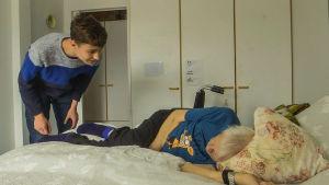 En kille hälsar på i rummet. Den äldre ligger på sängen och den studerande hälsar.