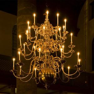 Närbild på en antik, gyllene ljuskrona med tända ljus.