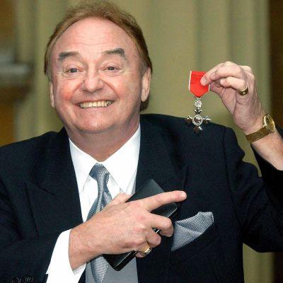Gerry Marsden hymyili kameralle brittiläisen imperiumin ritarikunnan merkin kanssa vuonna 2003.