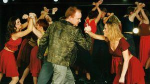 Skådespelare dansar med hotfulla miner.