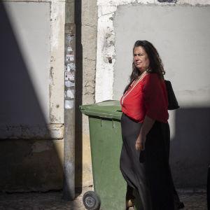 Maria Neves fotograferad utanför ett hus där fönstren murats igen.