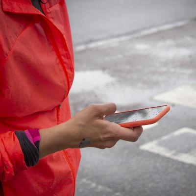 Amanda Kainulainen tarkistaa juoksunsa tuloksia Helsinki City Runin mobiilisovelluksesta juostuaan puolimaratonin.