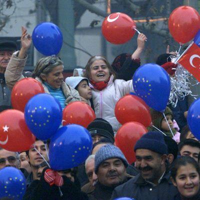 Ihmisiä heiluttamassa  Turkin lippuja ja EU-ilmapalloja.