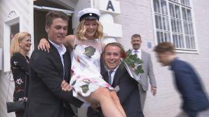 Färska studenten Minea Lassas bärs ut av storebror Fredrik Lassas.